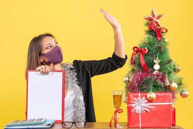 Kerstsfeer met charmante dame in pak die medisch masker draagt dat document hallo zegt in het bureau op geïsoleerd geel