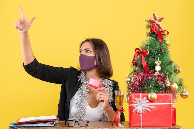 Kerstsfeer met charmante dame in pak die medische masker dragen met bankkaart in het kantoor op geel geïsoleerd