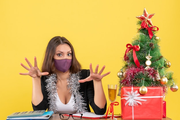 Kerstsfeer met charmante dame in pak medische masker dragen in het kantoor op geel geïsoleerd