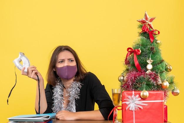 Kerstsfeer met doordachte mooie dame in pak met haar medische masker op kantoor