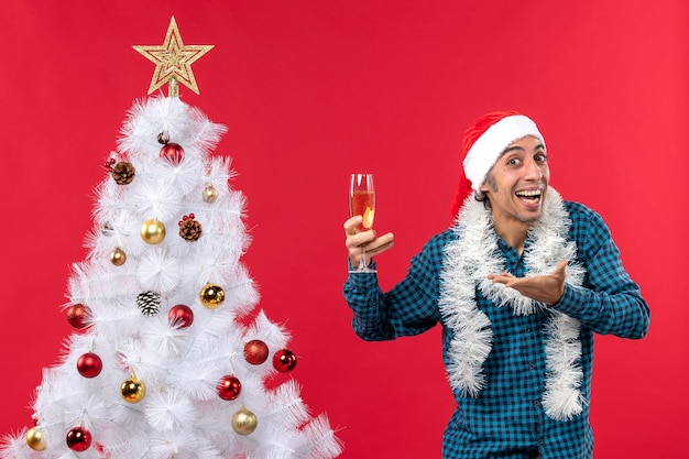 Kerstsfeer met emotionele jonge man met kerstman hoed in een blauw gestript shirt met een glas wijn en iets vragen in de buurt van de kerstboom