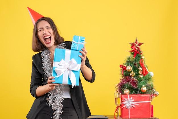 Kerstsfeer met emotionele mooie dame met kerstmuts met geschenken in het kantoor op geel