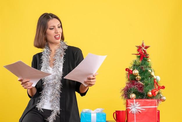 Kerstsfeer met emotionele mooie dame permanent in het kantoor en documenten in het kantoor op geel te houden