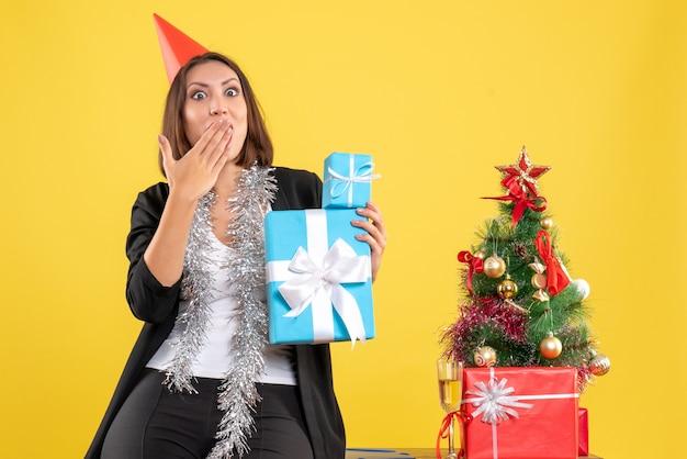 Kerstsfeer met emotionele verrast mooie dame met kerstmuts met geschenken in het kantoor op geel