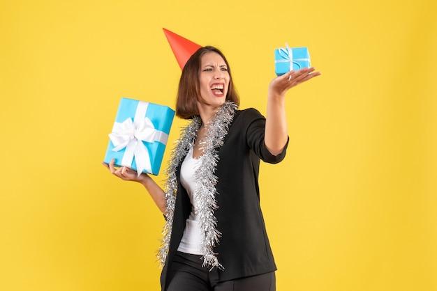 Kerstsfeer met emotionele zakelijke dame in pak met xsmas hoed kijken naar haar geschenken op geel