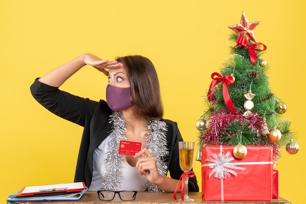 Kerstsfeer met geconcentreerde charmante dame in pak die medische masker draagt met bankkaart in het kantoor op geel