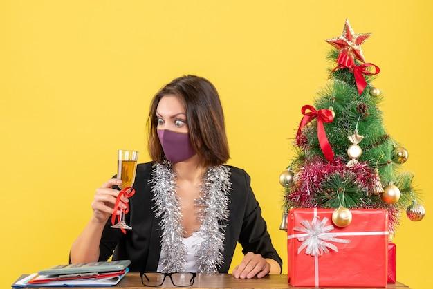 Kerstsfeer met geconcentreerde mooie dame in pak die medisch masker draagt en wijn in het bureau op geel verhoogt