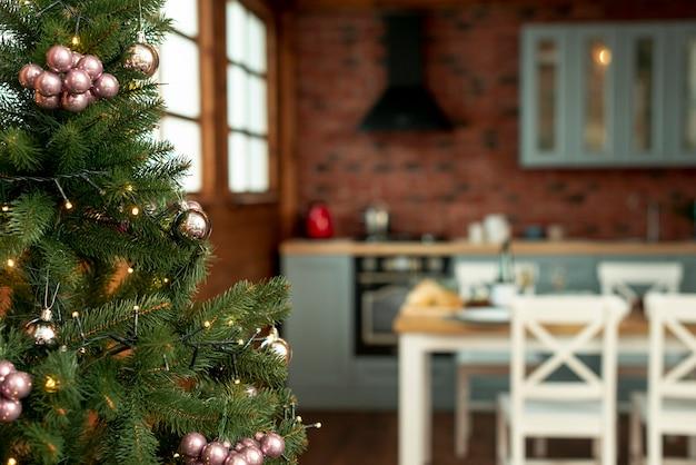 Kerstsfeer met gedecoreerde boom in de keuken