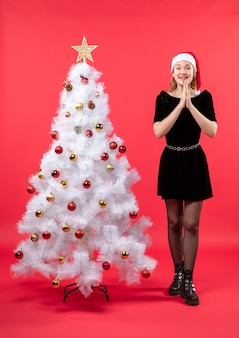 Kerstsfeer met gelukkige jonge vrouw in zwarte jurk en kerstman hoed staande in de buurt van witte nieuwe jaarboom