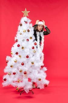 Kerstsfeer met geschokt jonge mooie dame in een zwarte jurk met kerstman hoed