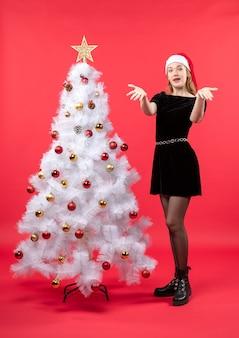 Kerstsfeer met geschokt jonge vrouw in zwarte jurk en kerstman hoed permanent in de buurt van witte kerstboom en iets beeldmateriaal te wijzen
