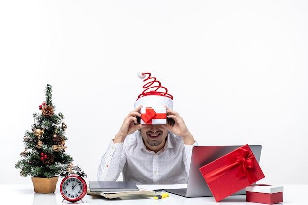 Kerstsfeer met grappige bedrijfspersoon die met de hoed van de kerstman zijn gift voor zijn gezicht op witte achtergrond houdt