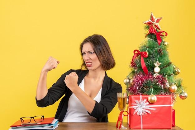 Kerstsfeer met jonge emotionele zakelijke dame zittend aan een tafel op kantoor