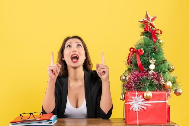Kerstsfeer met jonge geconcentreerde mooie vrouw die omhoog wijst en op kantoor zit