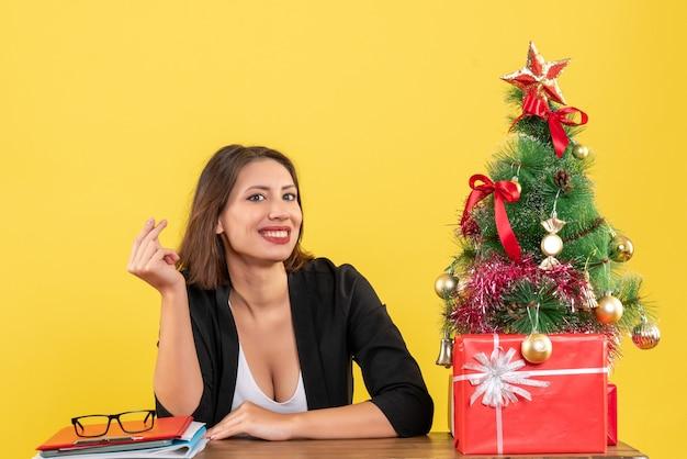 Kerstsfeer met jonge gelukkig mooie vrouw die geldgebaar maakt en op kantoor zit