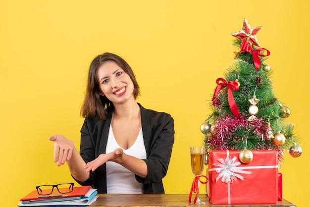 Kerstsfeer met jonge gelukkige emotionele zakelijke dame die haar bril aan een tafel in het kantoor op geel richt
