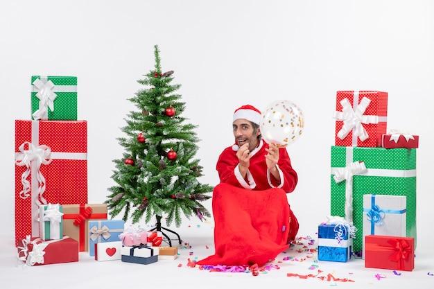 Kerstsfeer met jonge kerstman met ballon zittend in de buurt van kerstboom en geschenken in verschillende kleuren op witte achtergrond