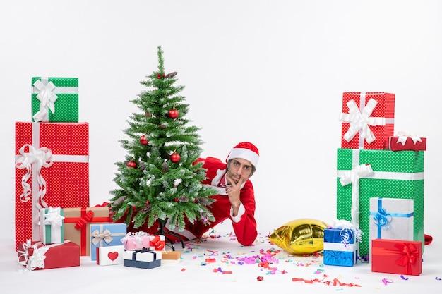 Kerstsfeer met jonge kerstman verstopt achter de kerstboom in de buurt van geschenken in verschillende kleuren op een witte achtergrond