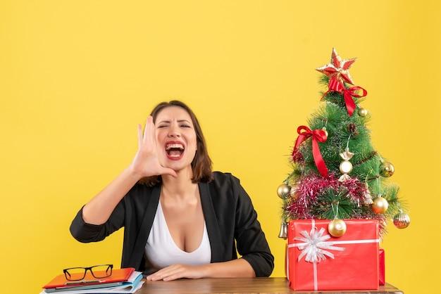 Kerstsfeer met jonge mooie vrouw die iets belt door op kantoor uit te kijken