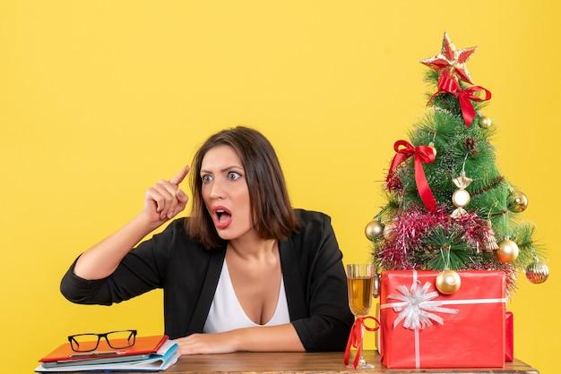 Kerstsfeer met jonge nerveuze gespannen boze emotionele bedrijfsdame die achter op geel wijst