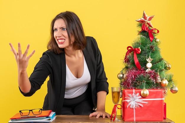 Kerstsfeer met jonge nerveuze gespannen boze emotionele zakelijke dame die iets op geel uitlegt