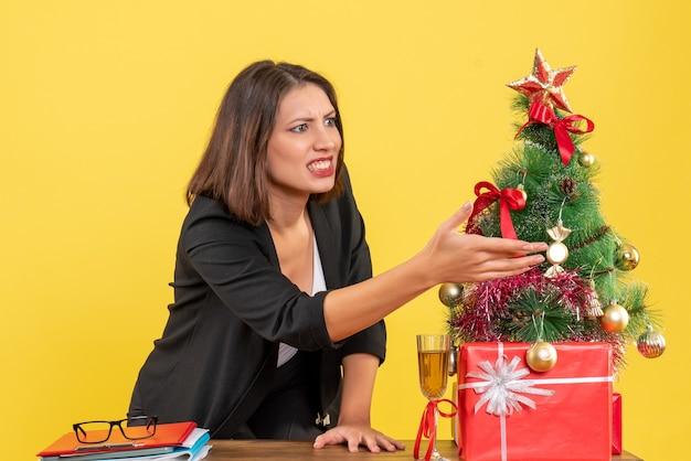 Kerstsfeer met jonge nerveuze gespannen boze emotionele zakelijke dame die iets op geel wijst