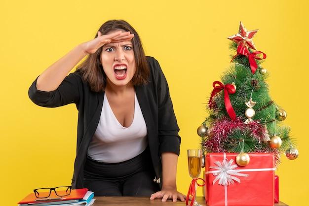 Kerstsfeer met jonge nerveuze gespannen boze emotionele zakelijke dame die naar iets op geel kijkt