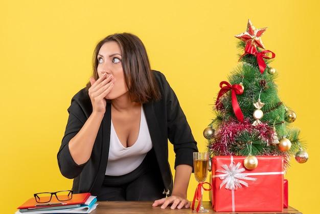 Kerstsfeer met jonge nerveuze gespannen verraste emotionele zakelijke dame die iets op geel bekijkt