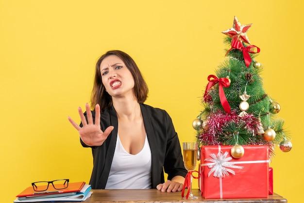 Kerstsfeer met jonge ontevreden serieuze boze emotionele bedrijfsdame die vijf op geel toont