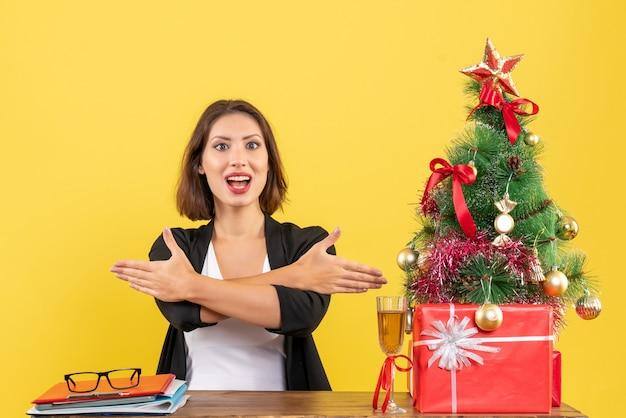 Kerstsfeer met jonge tevreden gelukkige emotionele zakelijke dame die iets wijst en aan een tafel op kantoor zit op geel