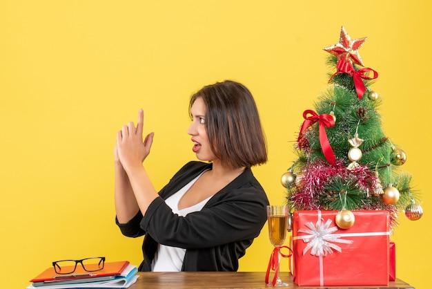 Kerstsfeer met jonge verwarde emotionele zakelijke dame die iets vraagt zittend aan een tafel op kantoor