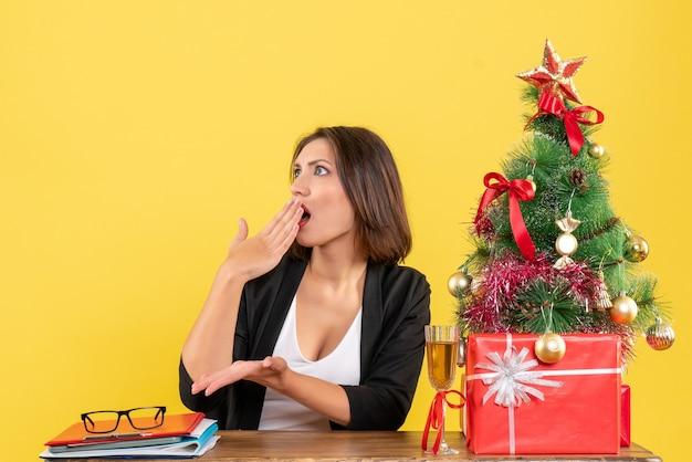 Kerstsfeer met jonge verwarde emotionele zakelijke dame zittend aan een tafel op kantoor
