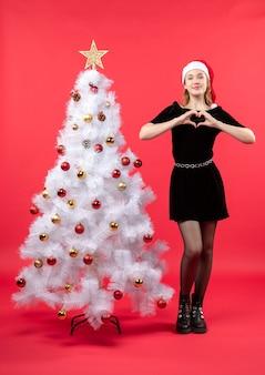 Kerstsfeer met jonge vrouw in zwarte jurk en kerstman hoed staande in de buurt van witte kerstboom en hart gebaar maken