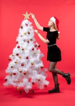 Kerstsfeer met jonge vrouw in zwarte jurk en kerstman hoed staande in de buurt van witte kerstboom en ster in boom te houden