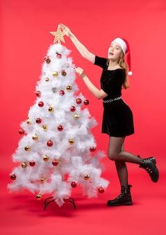 Kerstsfeer met jonge vrouw in zwarte jurk en kerstman hoed staande in de buurt van witte kerstboom en ster schikken