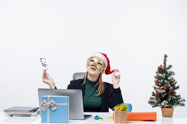 Kerstsfeer met jonge vrouw spelen met kerstman hoed houden bril en dragen masker zittend aan een tafel op witte achtergrond