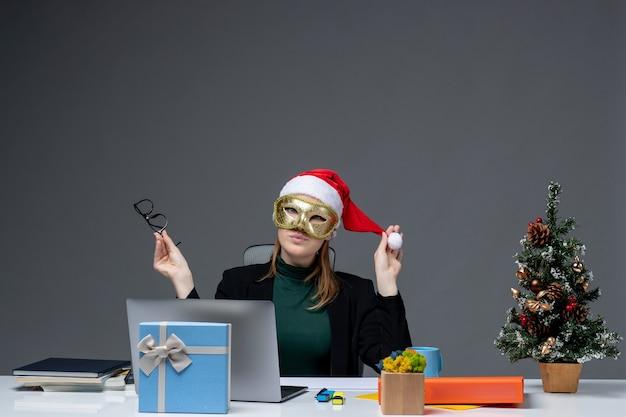 Kerstsfeer met jonge vrouw spelen met kerstman hoed houden bril en masker zittend aan een tafel op donkere achtergrond