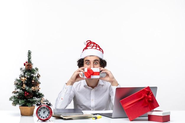 Kerstsfeer met jonge zakenman die met de hoed van de kerstman zijn gift op witte achtergrond houdt