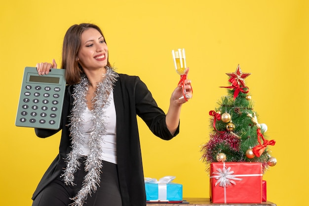 Kerstsfeer met lachende mooie dame permanent in het kantoor en rekenmachine verhogen van wijn in het kantoor op geel te houden