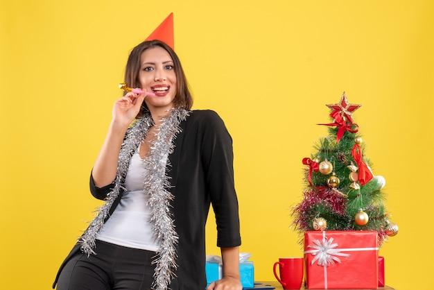 Kerstsfeer met lachende mooie dame poseren voor camera in het kantoor op geel