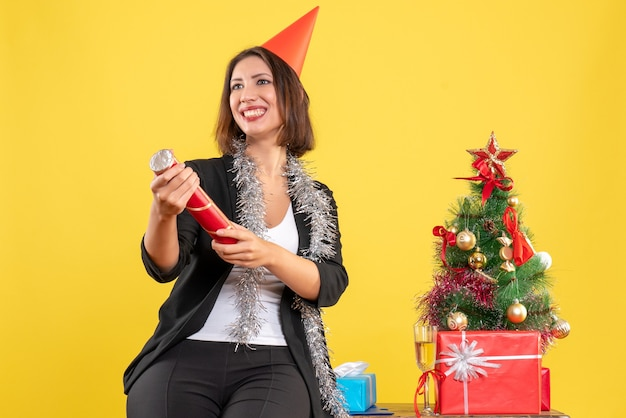 Kerstsfeer met mooie dame die zich gelukkig voelt op kantoor op geel