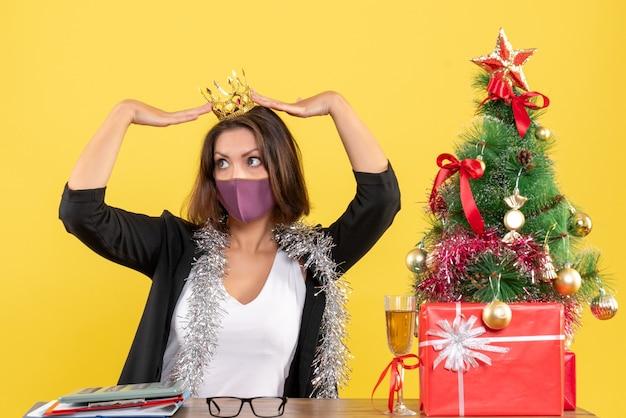 Kerstsfeer met mooie dame in pak die kroon met medisch masker draagt en gift in het bureau op geel houdt