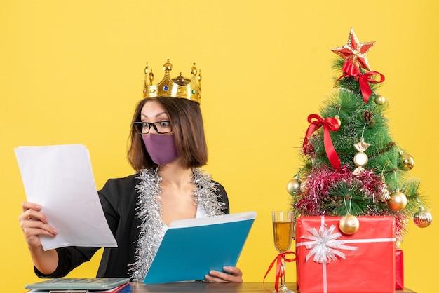 Kerstsfeer met mooie dame in pak met het dragen van kroon met haar medische masker documenten in het kantoor op geel controleren