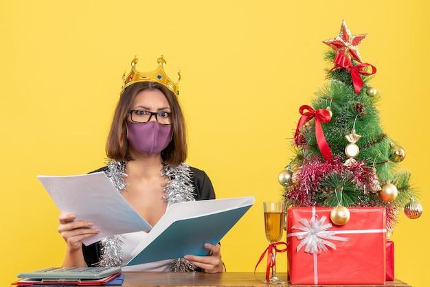 Kerstsfeer met mooie dame in pak met het dragen van kroon met haar medische masker met documenten in het kantoor op geel