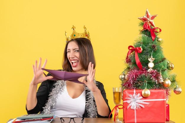 Kerstsfeer met mooie dame in pak met kroon die haar medisch masker in het kantoor op geel houdt