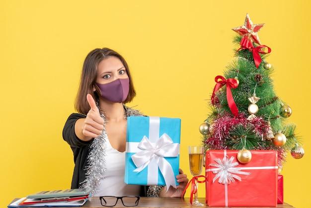 Kerstsfeer met mooie dame in pak met medisch masker en geschenk te houden in het kantoor ok gebaar maken op geel
