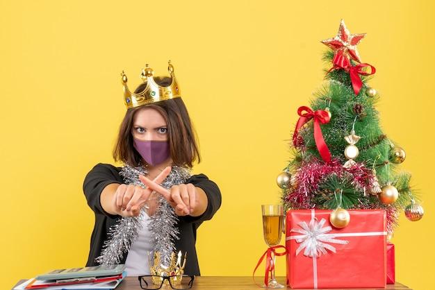 Kerstsfeer met mooie dame in pak met medisch masker en masker kruising vingers in het kantoor op geel dragen