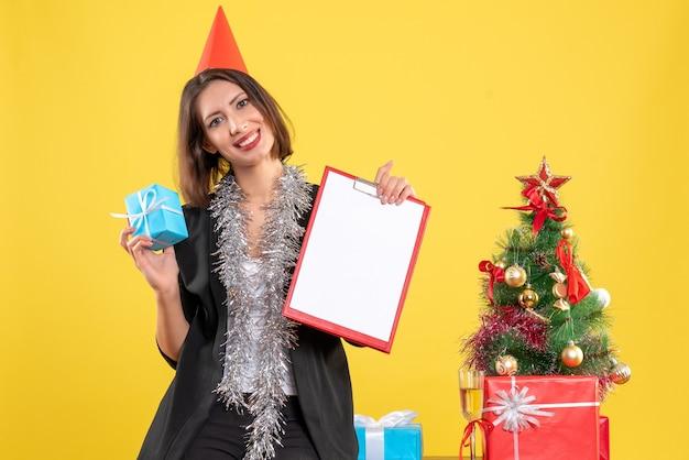 Kerstsfeer met mooie dame met document en cadeau in het kantoor op geel