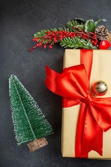 Kerstsfeer met mooie geschenken met boogvormig lint en dennentakken decoratie accessoires xsmas sok op een donkere achtergrond