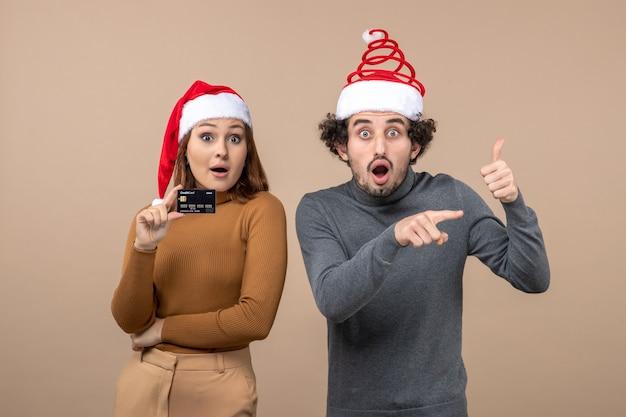 Kerstsfeer met opgewonden tevreden koel paar dat rode hoeden van de kerstman draagt vrouw die bankkaart kerel toont die iets richt